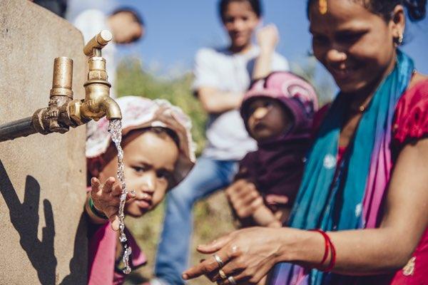 Kind an einem Trinkwasserbrunnen in Nepal